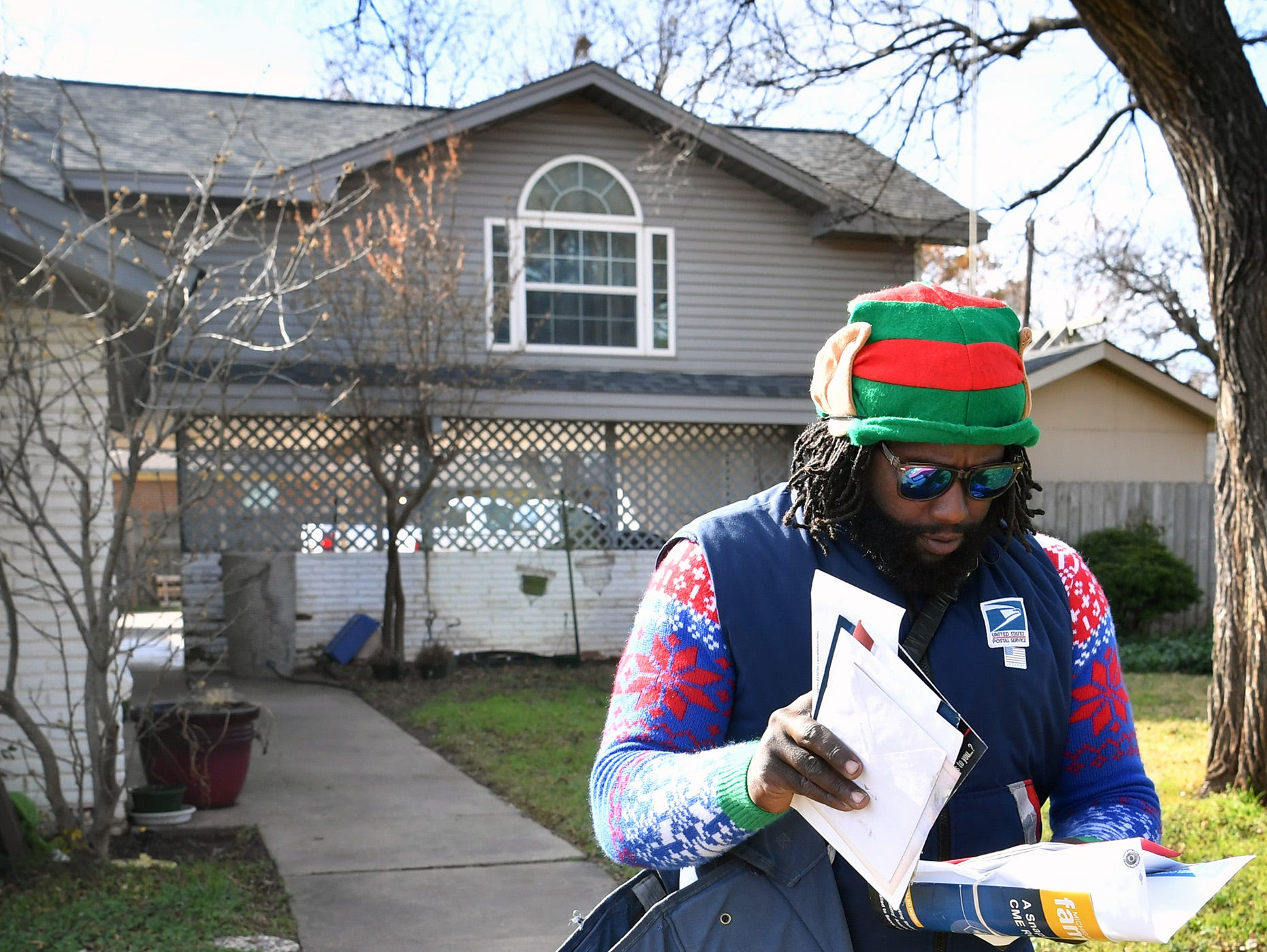 Christmas sweaters and elf hats are just a few things that help mail carrier Joe Forbins spread holiday cheer while walking his mail route each day.