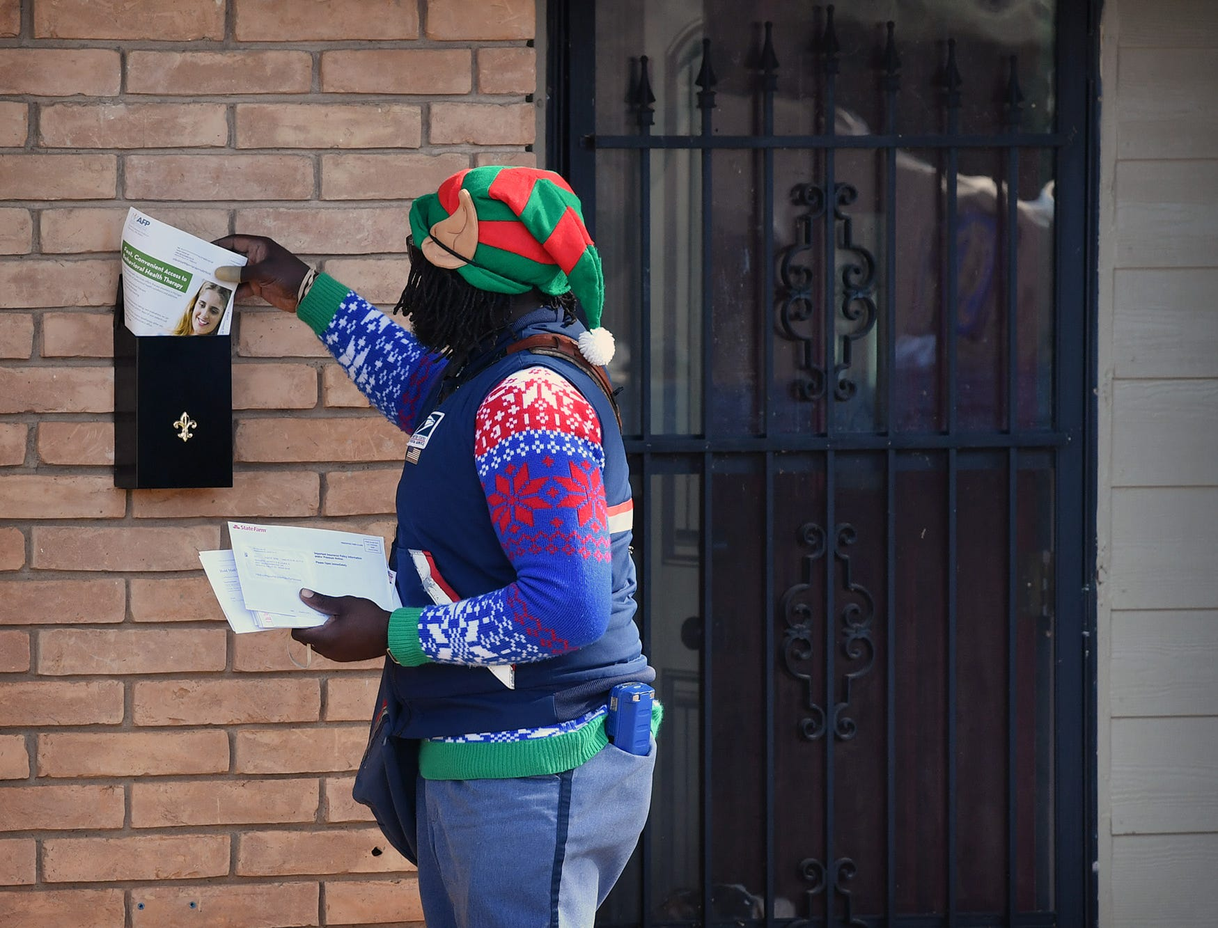 Mail carrier Joe Forbins is popular with the customers on his route  as he delivers their mail with a cheerful smile, Christmas sweater and an elf hat.