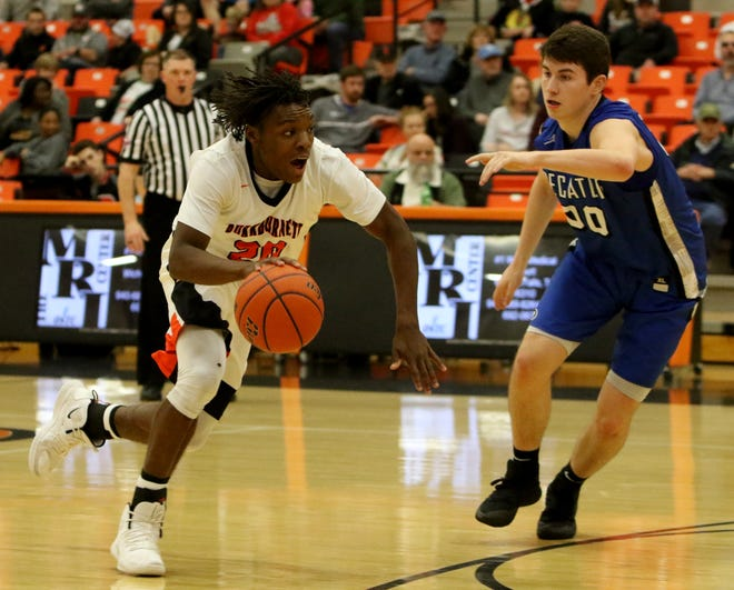 Burkburnett's Kendarious Horton drives to the basket by Decatur's Grayson Harris Thursday, Dec. 20, 2018, in Burkburnett.