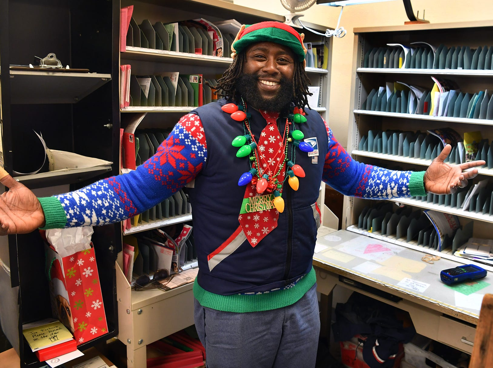 Joe Forbins, a mail carrier for the southwest area of Wichita Falls, enjoys spreading holiday cheer, embellishing his uniform with Christmas sweater, elf hat and ears, and a fun tie.