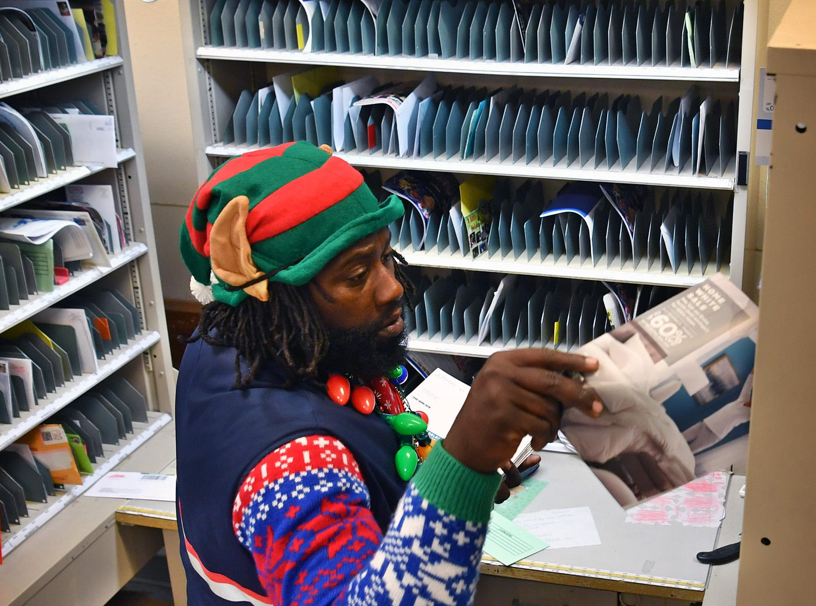 Postal carrier Joe Forbins sorts mail Friday morning. Around Christmas, Forbins spreads cheer along the way with a elf hat, Christmas sweater and candy for those on his route of more than 600 addresses.