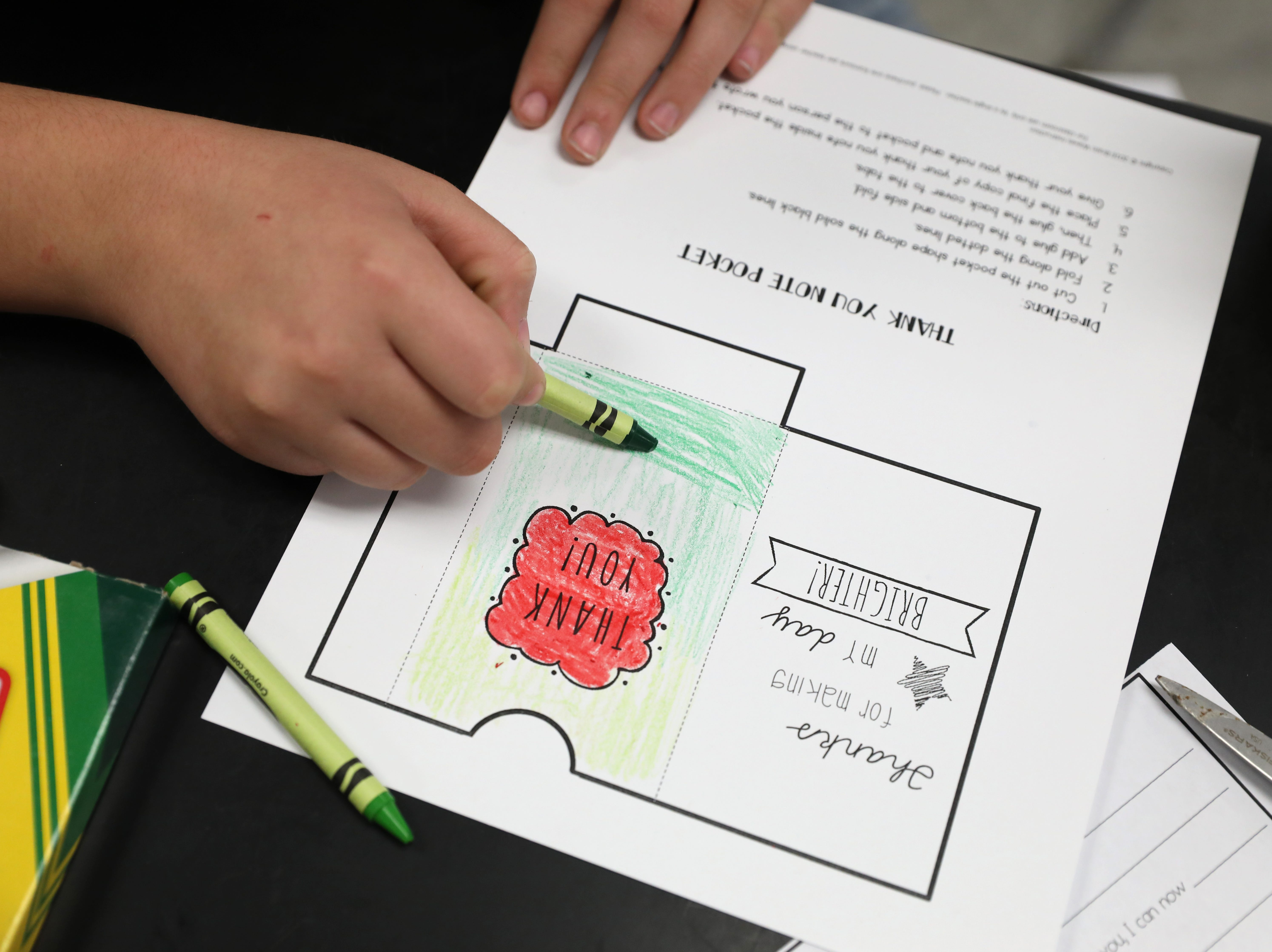 A student colors a thank you pocket during Roseville Elementary School's dude. be nice program.