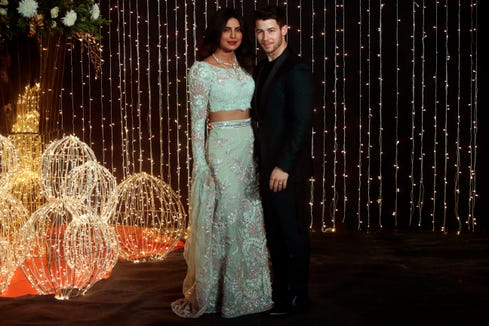 Bollywood actress Priyanka Chopra and musician Nick Jonas pose for photographs at their wedding reception in Mumbai, India, Thursday, Dec 20, 2018.