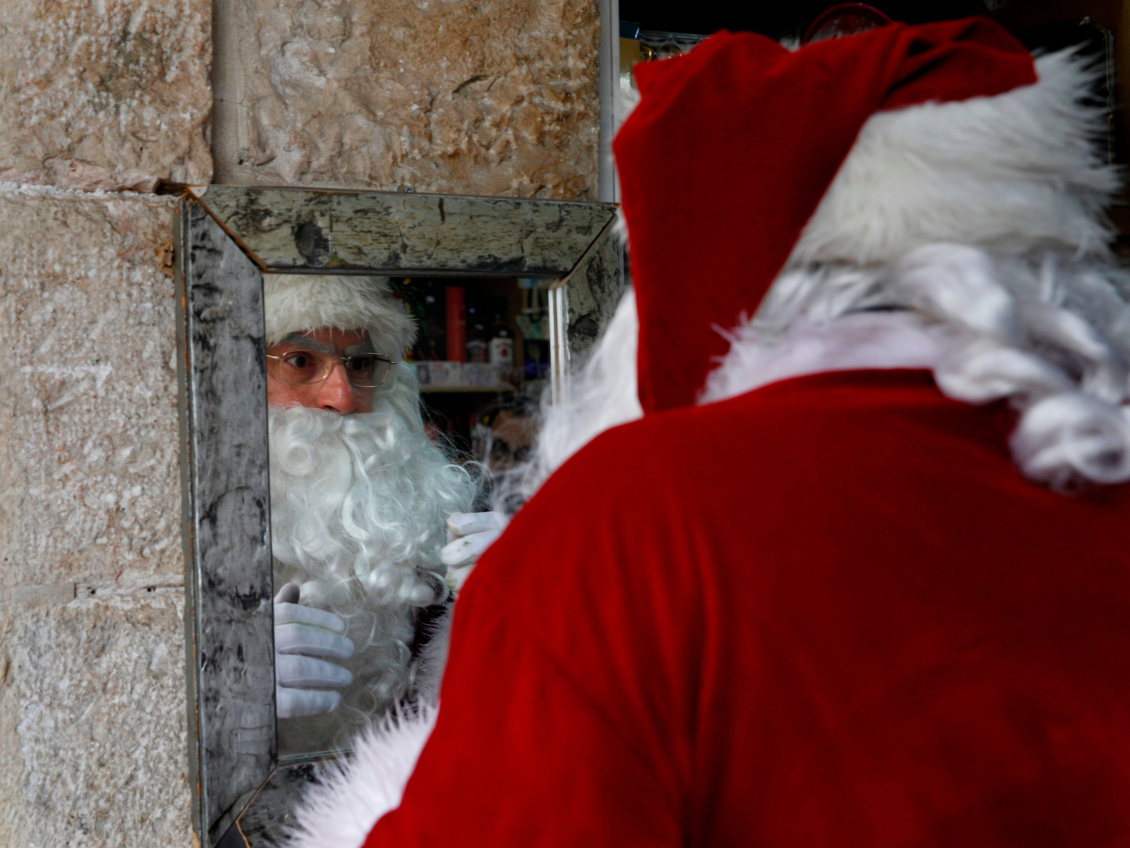 A man dressed as Santa Claus checks his look at a grocery store in Jerusalem's Old City on Dec. 20, 2018.