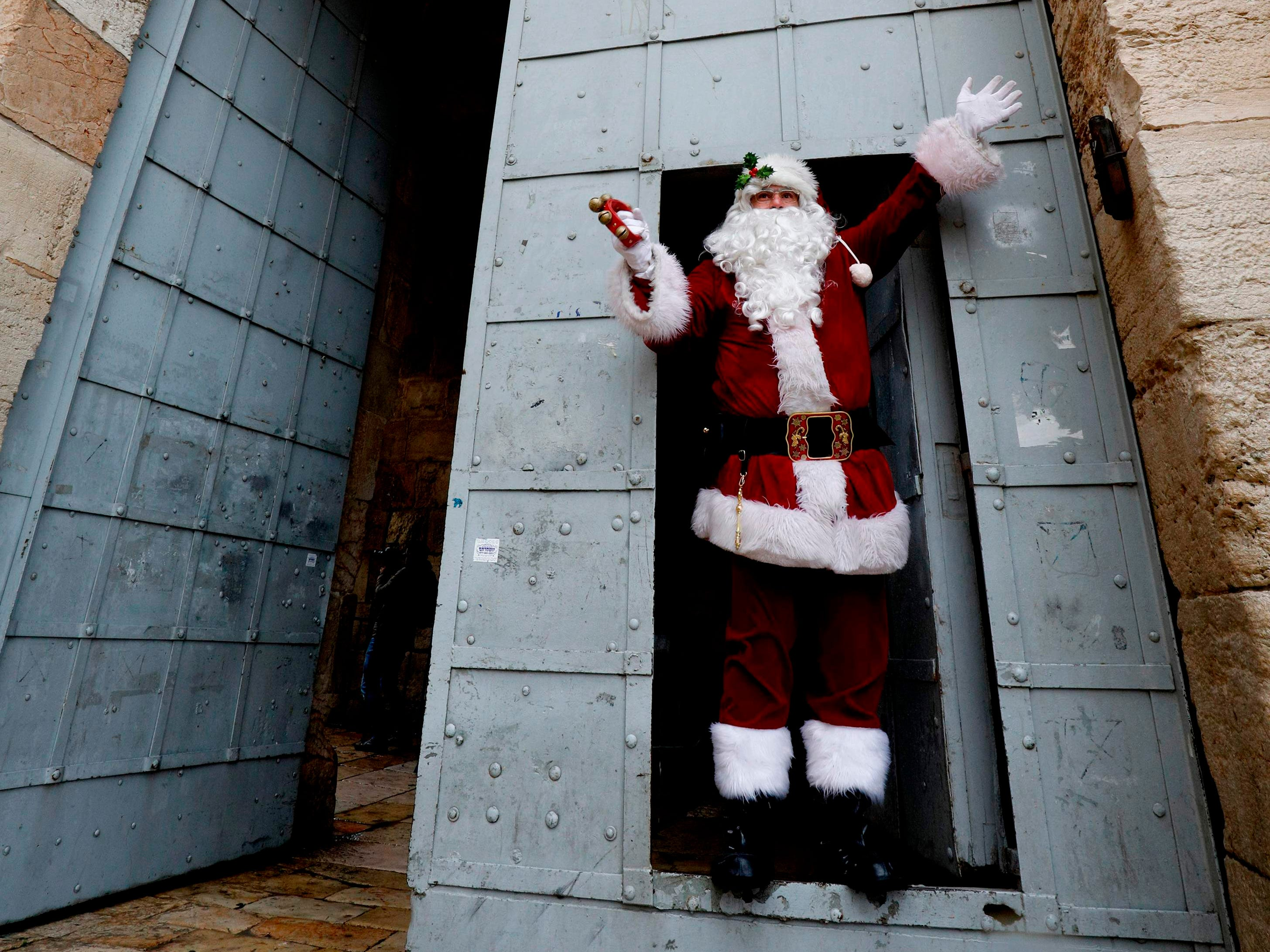 A man dressed as Santa Claus stands at the door of Jaffa Gate in Jerusalem's Old City on Dec. 20, 2018.