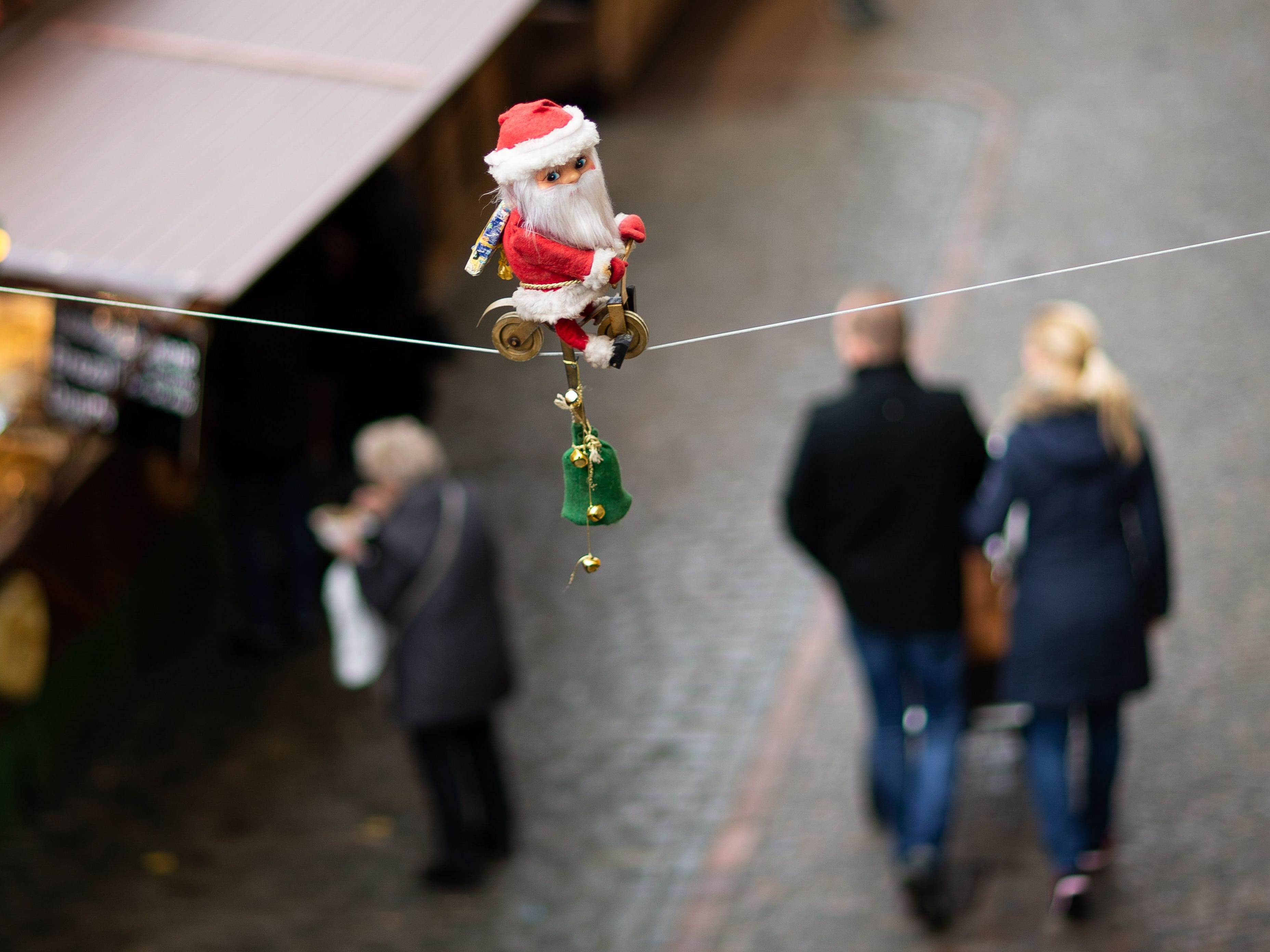 A small Santa Claus figurine cycles on a rope that stretches over the Christmas market in Osnabrueck, Germany, on Dec. 19, 2018.