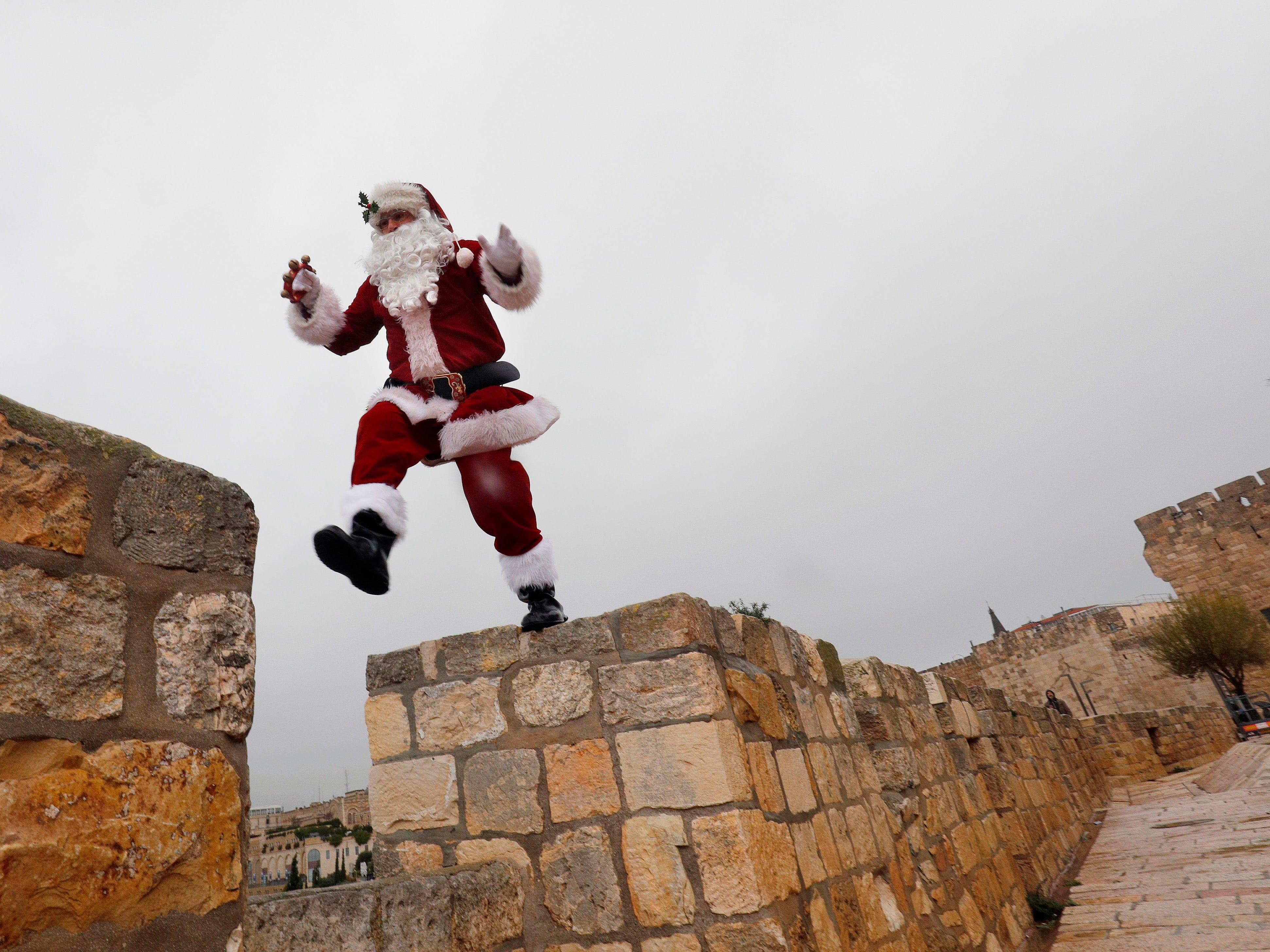 A man dressed as Santa Claus waves as he walks along Jerusalem's Old City Ottoman walls on Dec. 20, 2018.
