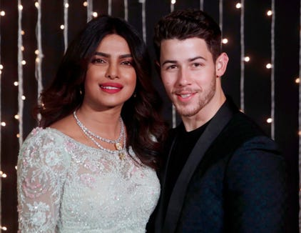 Bollywood actress Priyanka Chopra and musician Nick Jonas stand for photographs at their wedding reception in Mumbai, India, Thursday, Dec 20, 2018.