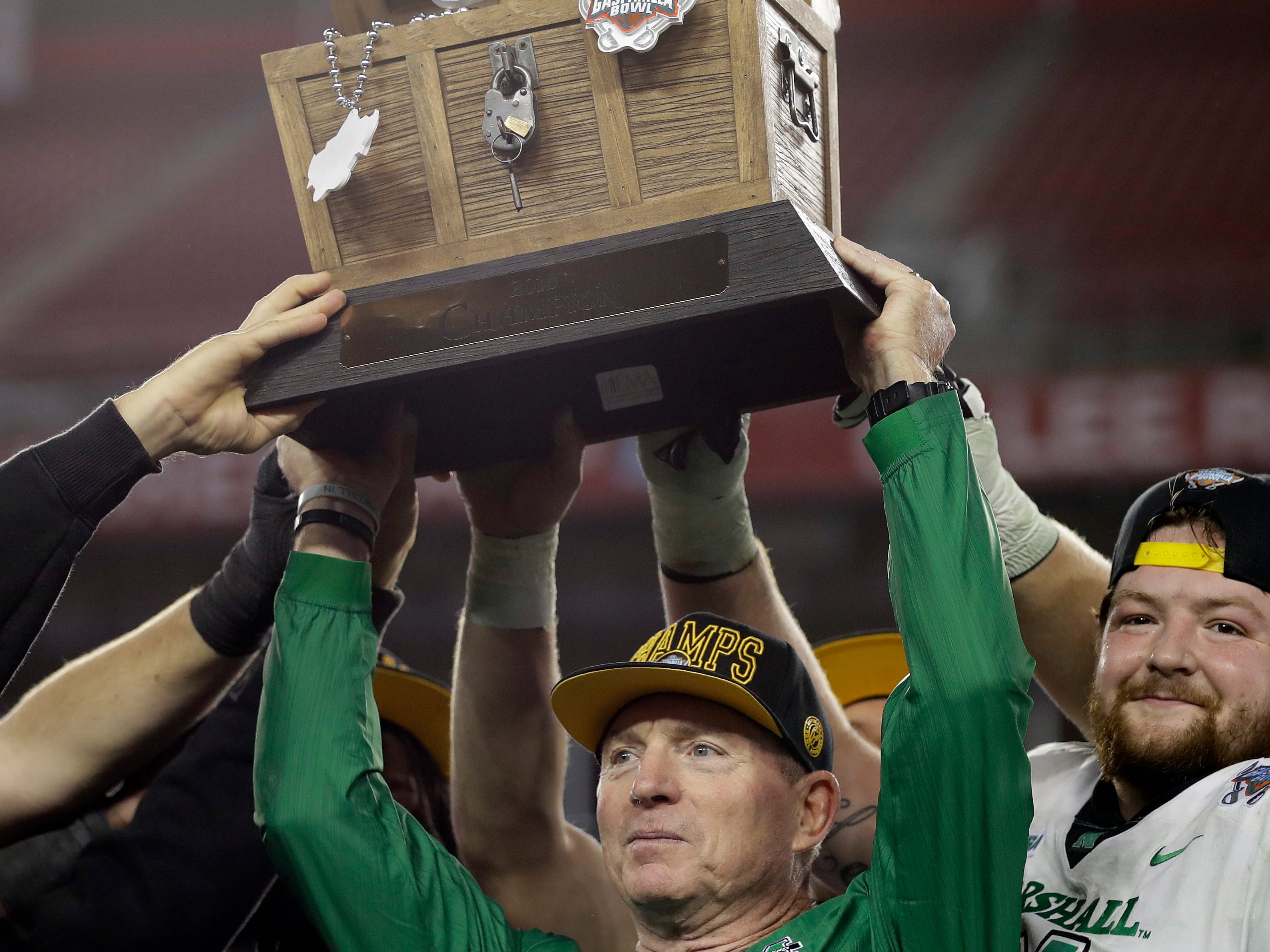 Marshall coach Doc Holliday holds up the Gasparilla Bowl  trophy after Marshall defeated South Florida, 38-20, in Tampa, Fla.