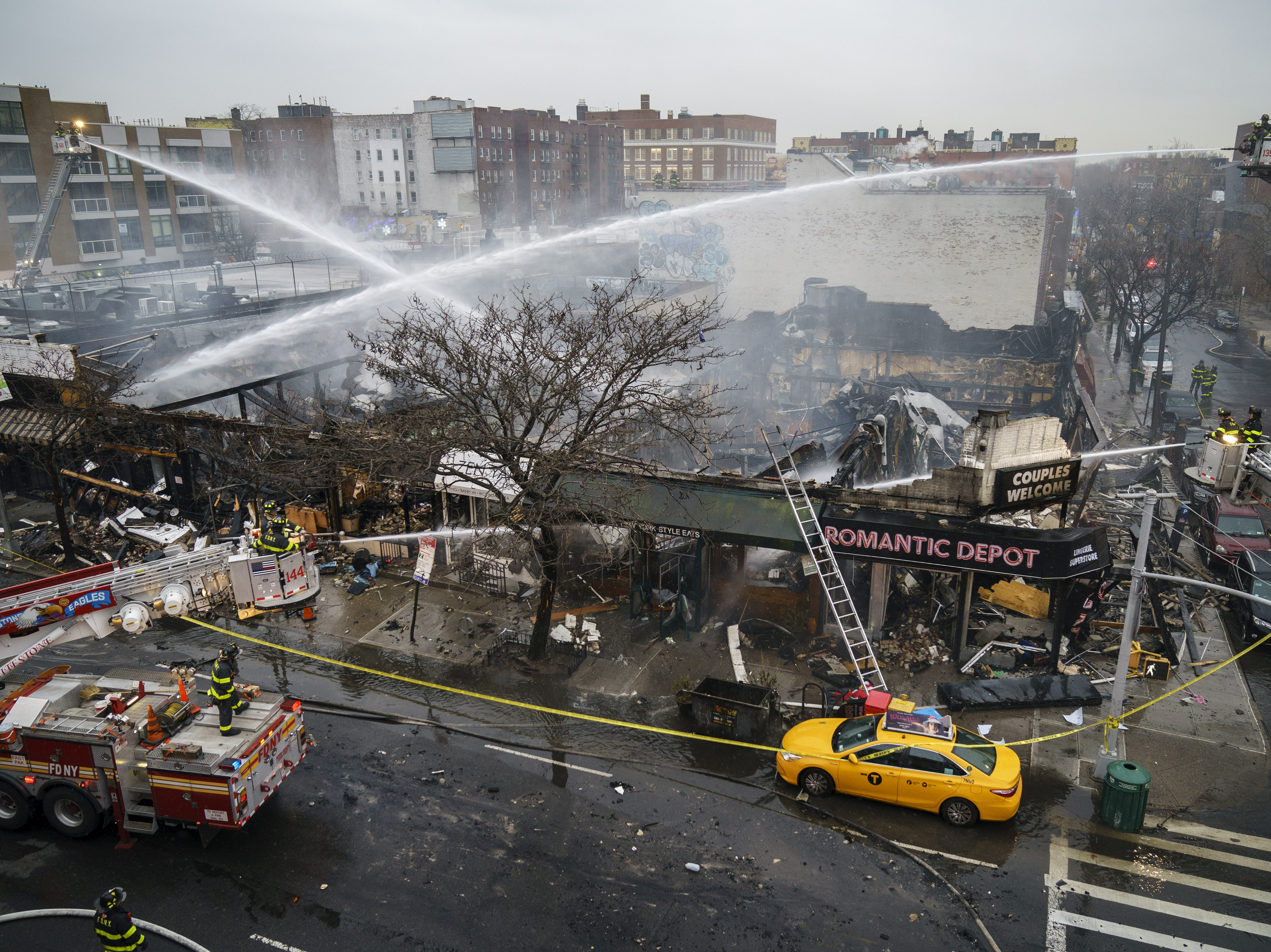 Dec. 13, 2018: Firefighters work to put out the smoldering remains of an overnight fire that engulfed six businesses on Queens Boulevard in the Queens borough of New York City. A dozen people were injured in the fire, including six firefighters.