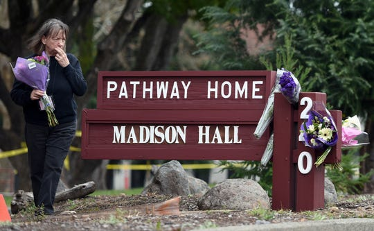 A woman who declined to give her name reacts while placing flowers at a sign outside the Pathway Home in Yountville, California, on March 10.