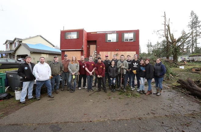 Volunteers, neighbors and family members pose for quick photos as they help clean up Tiburon Court in Port Orchard on Friday. The Mueller family, who lives in the red home, is one of the many families for whom the holidays will be upended this year, after a tornado devastated the neighborhood on Dec. 18.
