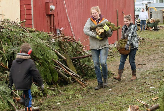 Tori Lawrence, front, and Jasmin Mueller, 16, haul wood debris from the yard of Jasmin's family's home on Friday. Lawrence — who is from Arizona and is in the area visiting her boyfriend — bought some work gloves and just came to the neighborhood to help out.