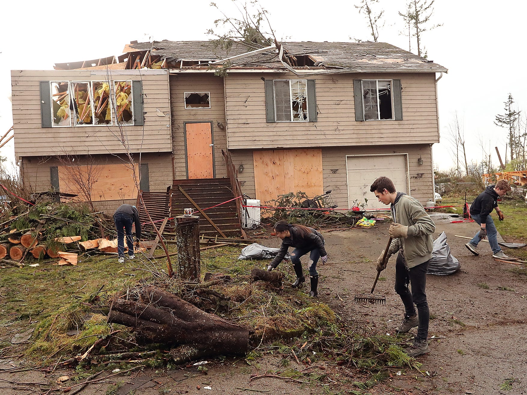 South Kitsap High School student volunteers (left to right) Dylan Rockafield, Kaili Arruda, Owen Chaffin, and Brad King rake and remove debris from the front yard of the Crain family's tornado damaged home on Tiburon Ct. in Port Orchard on Friday, December 21, 2018.