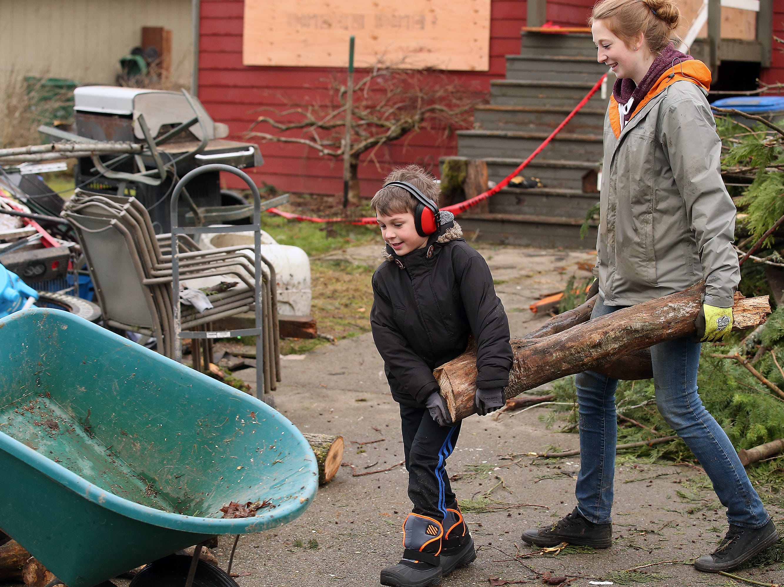 Casey Stone, 9, and Tori Lawrence work together to carry a large log to the Mueller's front yard as they help cleanup tornado debris on Tiburon Ct. in Port Orchard on Friday, December 21, 2018. Stone is a neighbor of the Muellers while Lawrence - who is from Arizona and is in the area visiting her boyfriend - bought some work gloves and just came to the neighborhood to help out.