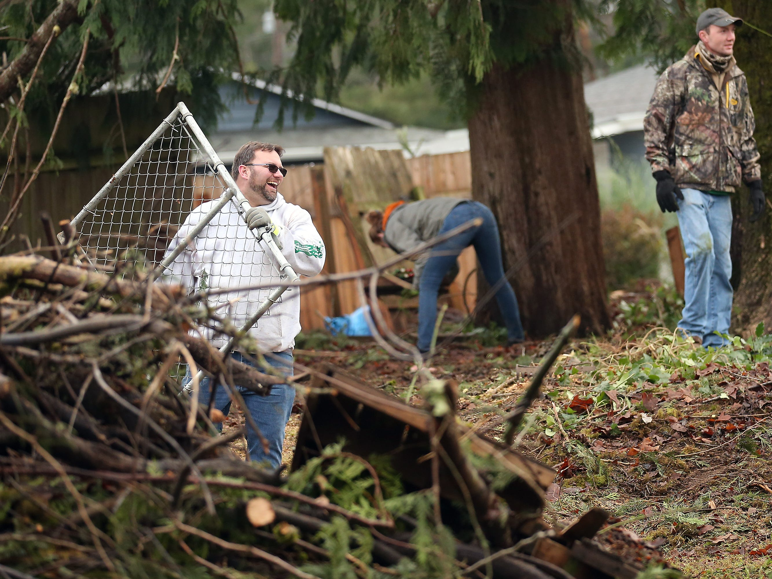 John Mueller laughs as he carries a gate through his storm ravaged backyard as family, friends, neighbors and volunteers clean up storm debris at his Tiburon Ct. home in Port Orchard on Friday, December 21, 2018.