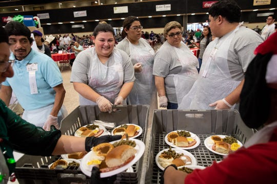 Volunteers prepare plates of food for the H-E-B's 30th Feast of Sharing held at the American Bank Center on Saturday, Dec. 22, 2018.