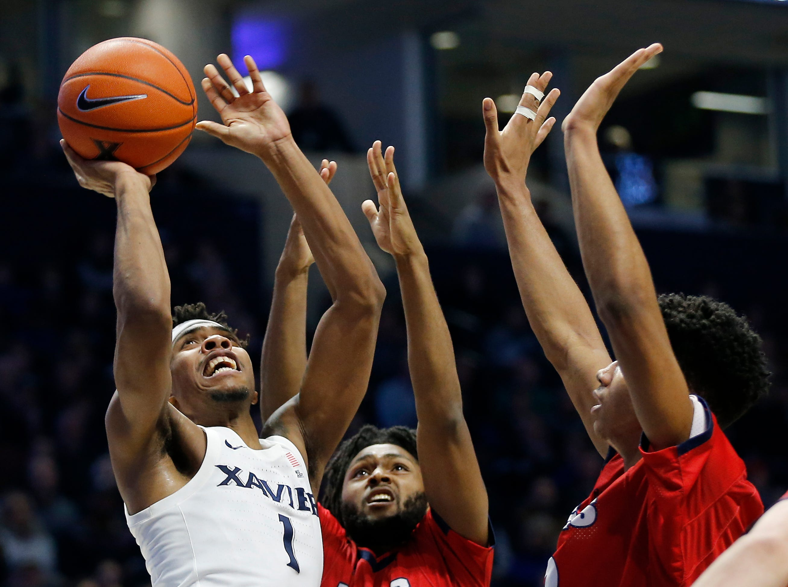 Xavier Musketeers guard Paul Scruggs fights to put up a shot under the basket in the second half.