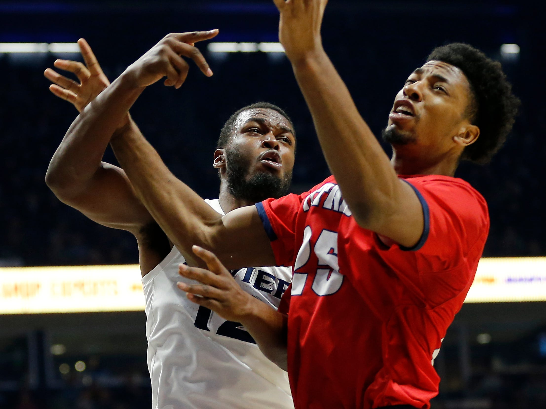 Xavier Musketeers forward Dontarius James and Detroit Mercy forward Gerald Blackshear Jr. collide going for a rebound in the first half.