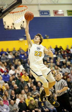 Moeller forward Will McCracken goes up for a dunk during the Crusaders' basketball game against  Covington Cathoic , Friday, Dec. 22,2018.
