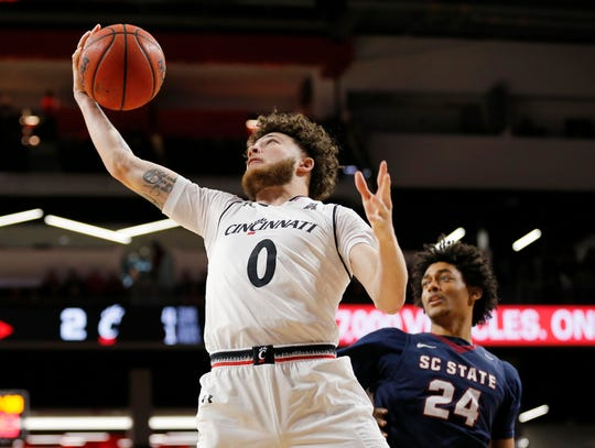 Cincinnati Bearcats guard Logan Johnson (0) pulls in a rebound in the first half of the NCAA basketball game between the Cincinnati Bearcats and the South Carolina State Bulldogs at Fifth Third Arena in Cincinnati on Saturday, Dec. 22, 2018. The Bearcats led 35-16 at halftime.
