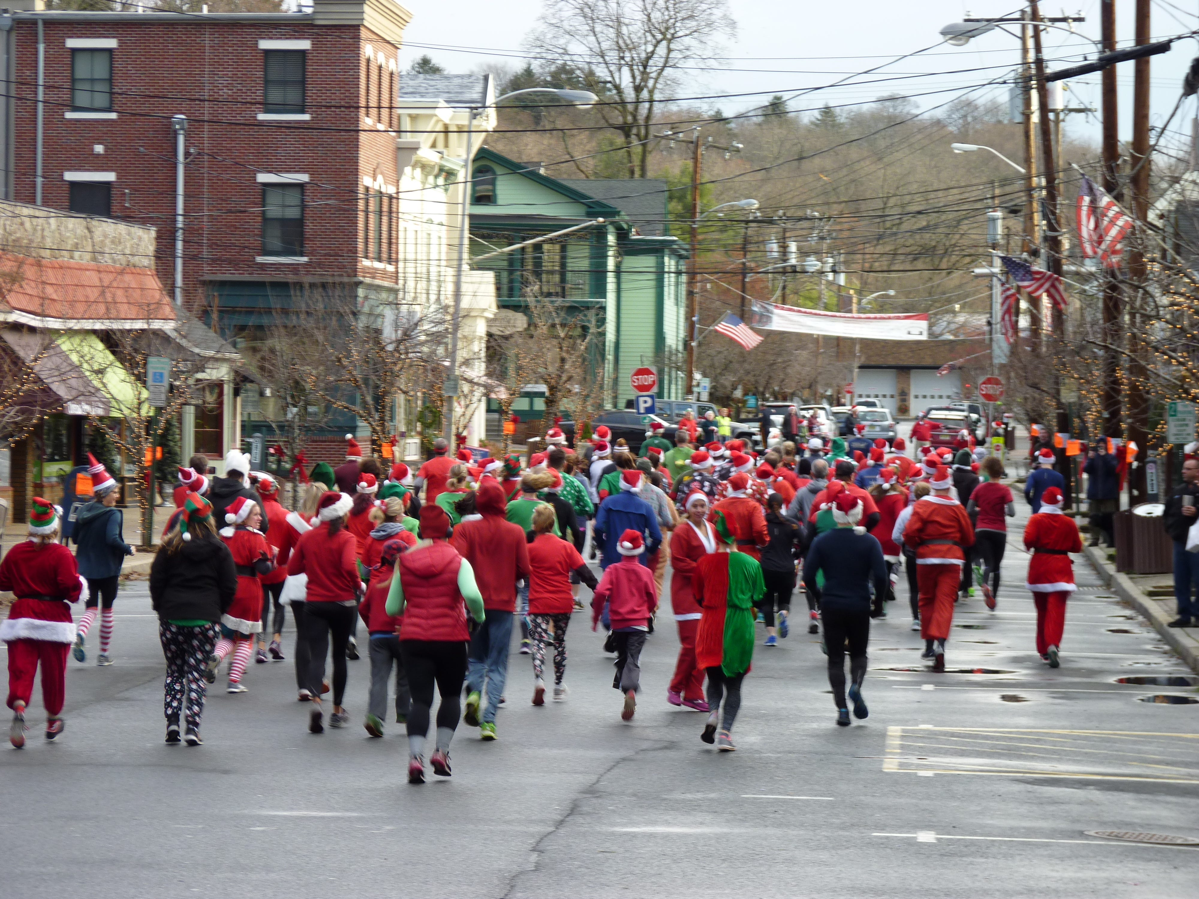 "More than 1,000 people came out to Clinton on Saturday, Dec. 22 dressed in festive costumes to run in the ""Run Before Christmas"" SantaCon 8K race to raise funds for the Red Mill Museum Village. Nick Muscavage/Staff Photo"