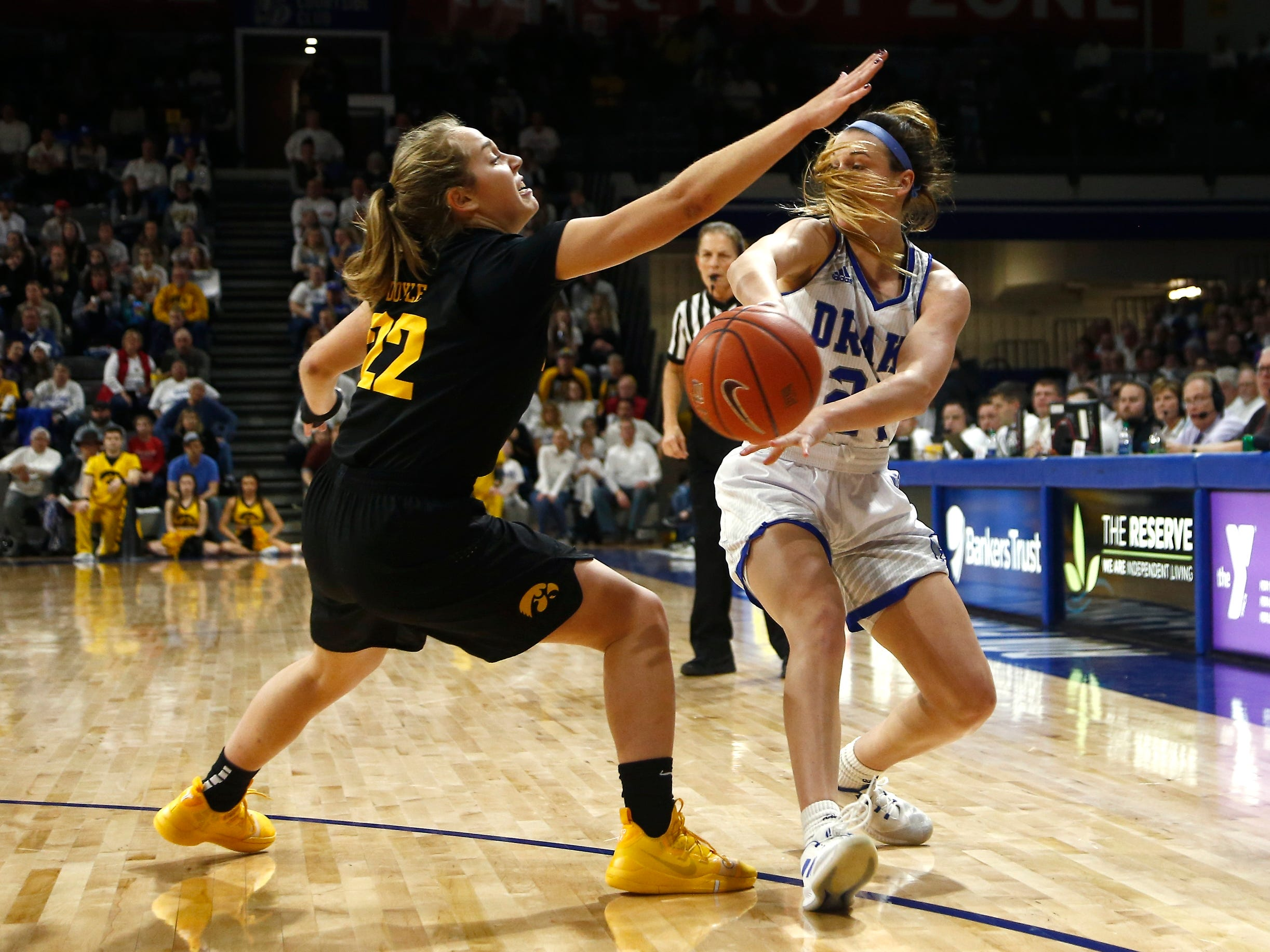 Drake's SammieBachrodt (21) passes around Iowa's Kathleen Doyle (22) during their basketball game on Friday, Dec. 21, 2018, in Des Moines. Drake takes a 45-43 lead into halftime.