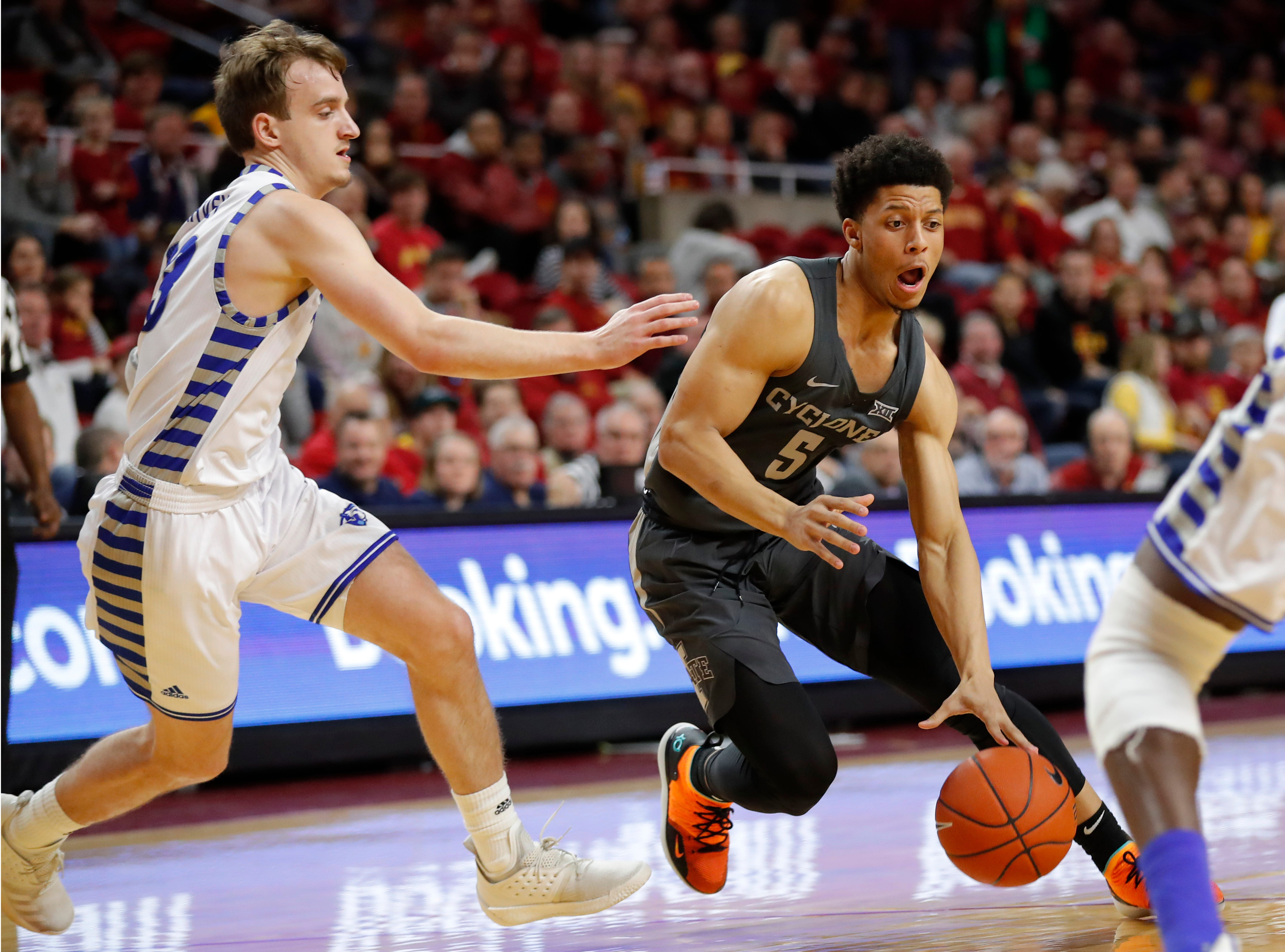 Iowa State guard Lindell Wigginton (5) drives past Eastern Illinois guard Ben Harvey, left, during the first half of an NCAA college basketball game Friday, Dec. 21, 2018, in Ames, Iowa.