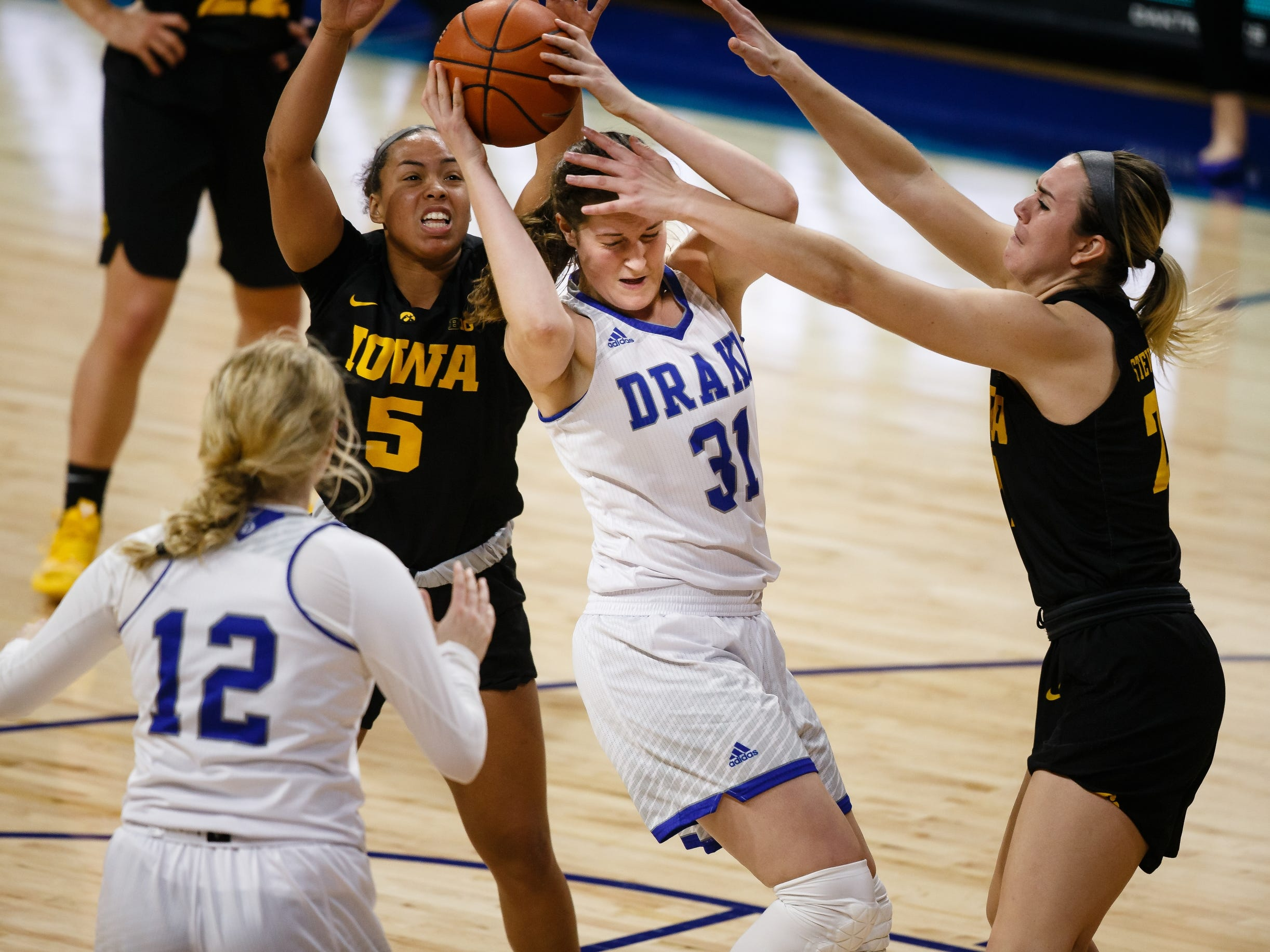 Drake's MonicaÊBurich (31) fights for possession with Iowa's Alexis Sevillian (5) and Iowa's Hannah Stewart (21) during their basketball game on Friday, Dec. 21, 2018, in Des Moines. Iowa would go on to defeat Drake 91-82.