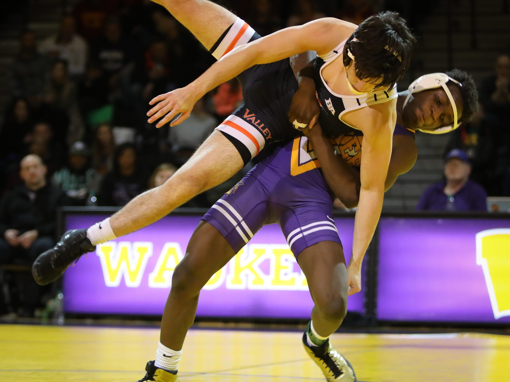 Valley senior Jackson Lukehart takes down Waukee sophomore Jermaine Sammler in the 145-pound weight class during a high school wrestling meet between the Valley Tigers and the Waukee Warriors at Waukee High School on Dec. 20, 2018 in Waukee, Iowa.