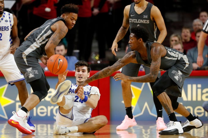 Eastern Illinois forward Rade Kukobat, center, passes the ball between Iowa State defenders Zion Griffin, left, and Zoran Talley Jr., right, during the second half of an NCAA college basketball game Friday, Dec. 21, 2018, in Ames, Iowa. Iowa State won 101-53.