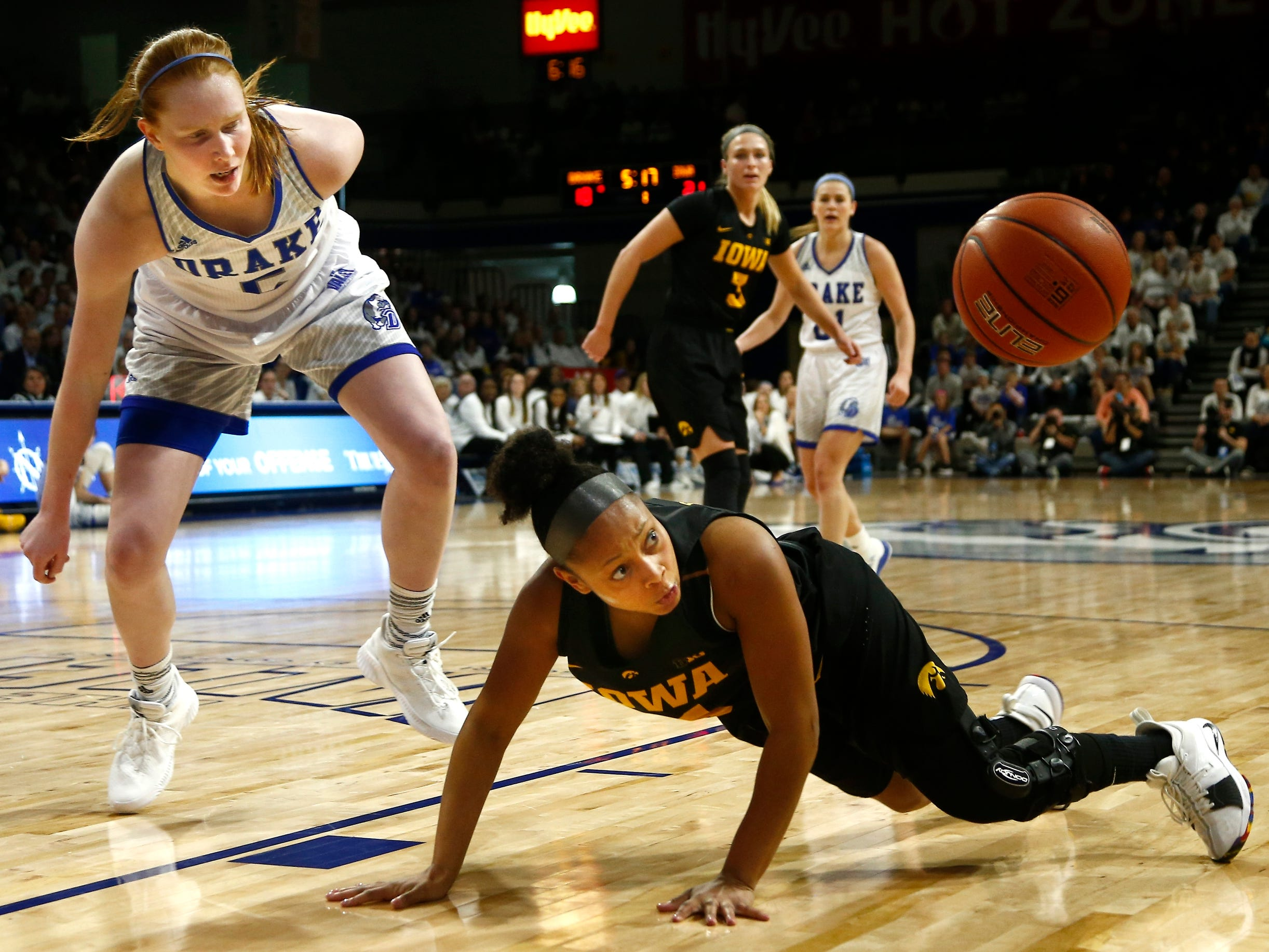 Iowa's Tania Davis (11) looks over at a loose ball as Drake's Becca Hittner (5) does the same during their basketball game on Friday, Dec. 21, 2018, in Des Moines. Drake takes a 45-43 lead into halftime.