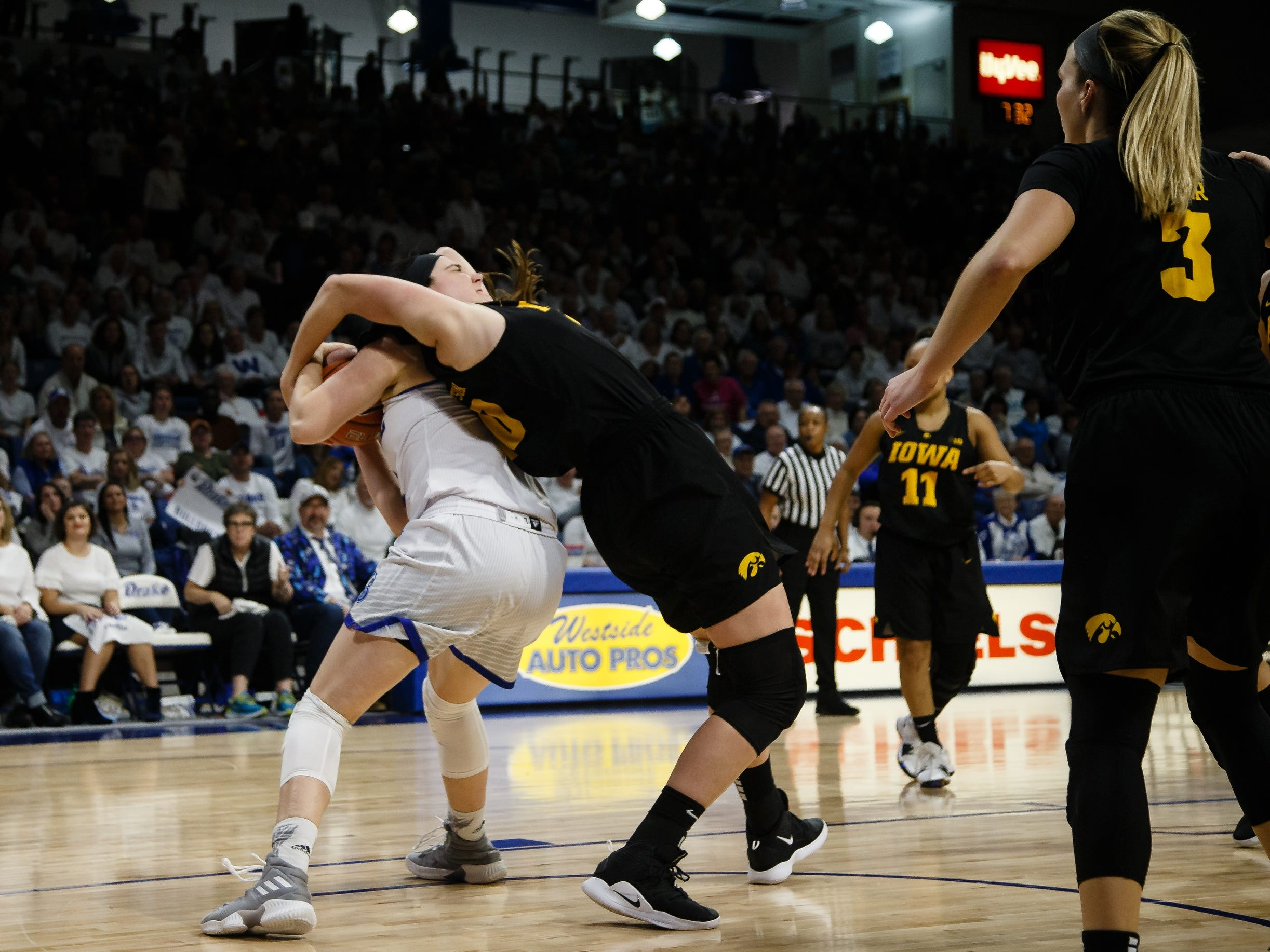 Drake's MonicaÊBurich (31) and Iowa's Megan Gustafson (10) both come down with a rebound during their basketball game on Friday, Dec. 21, 2018, in Des Moines. Iowa would go on to defeat Drake 91-82.