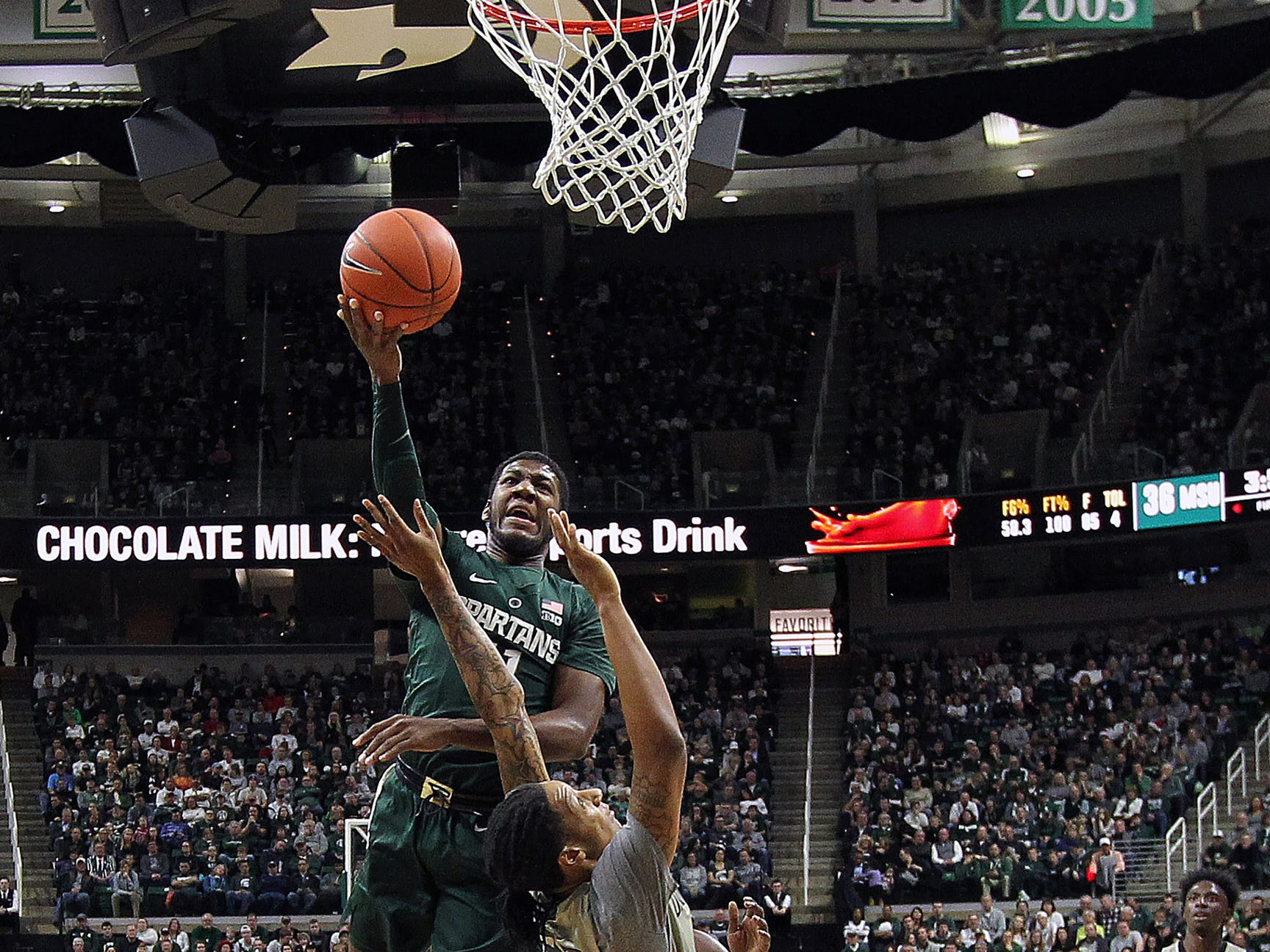 Michigan State Spartans forward Aaron Henry (11) lays the ball up over Oakland Golden Grizzlies guard Tray Maddox Jr. (2) during the first half of a game at the Breslin Center.