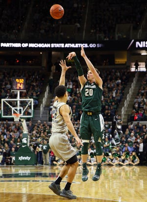 Michigan State Spartans guard Matt McQuaid (20) attempts a three-point basket over Oakland Golden Grizzlies guard Jaevin Cumberland (21) during the second half of a game at the Breslin Center.