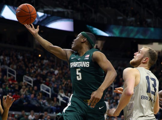 Michigan State Spartans guard Cassius Winston (5) grabs a rebound over Oakland Golden Grizzlies center Brad Brechting (13) during the second half of a game at the Breslin Center.