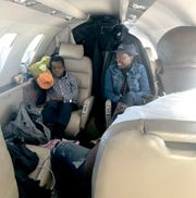 Gaelson Augustin on the plane with Myrtha Montas, a registered nurse at Michigan Medical Center, headed to Detroit for treatment.