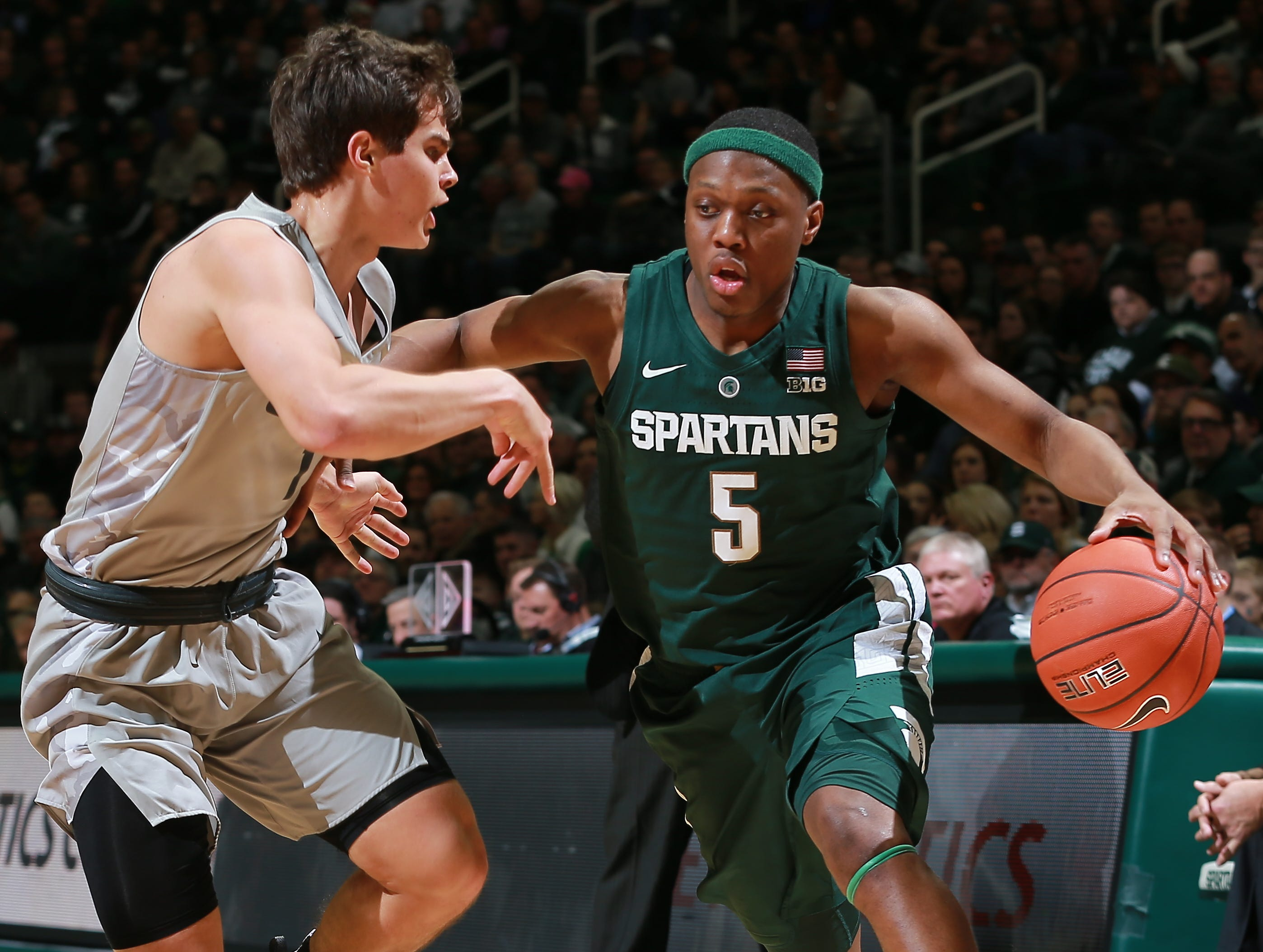 Cassius Winston #5 of the Michigan State Spartans handles the ball while defended by Braden Norris #1 of the Oakland Golden Grizzlies in the first half at Breslin Center on December 21, 2018 in East Lansing, Michigan.