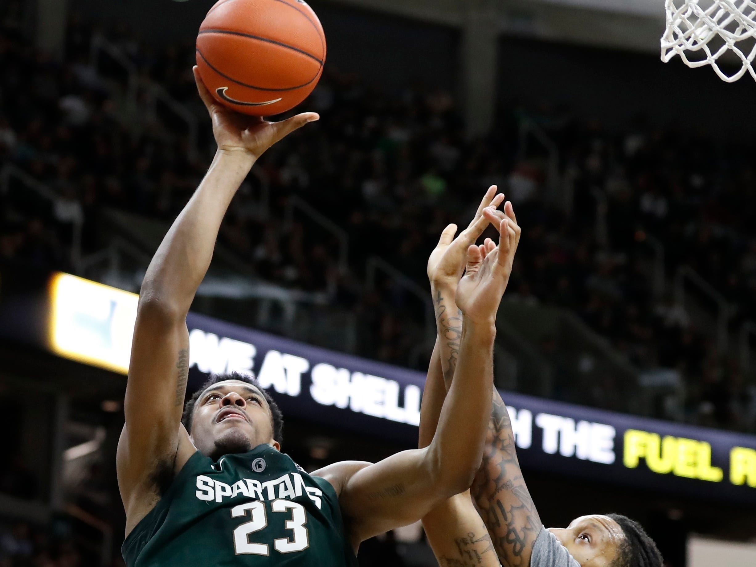 Michigan State forward Xavier Tillman (23) shoots as Oakland forward James Beck (22) defends during the second half of an NCAA college basketball game, Friday, Dec. 21, 2018, in East Lansing, Mich.