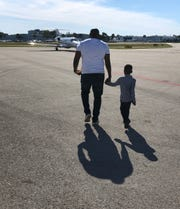 Alain Charles, Haitian Director at the orphanage, walks with Gaelson Augustin to the plane in Haiti, bound for Detroit.