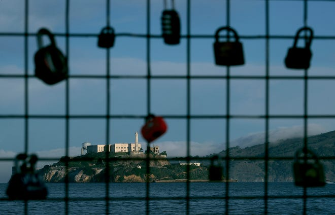 Alcatraz Island is shown behind a locks on a pier fence in San Francisco, Saturday, Dec. 22, 2018. The company that provides ferry services to Alcatraz Island kept its daytime tours but canceled its behind-the-scenes and night tours for Saturday.