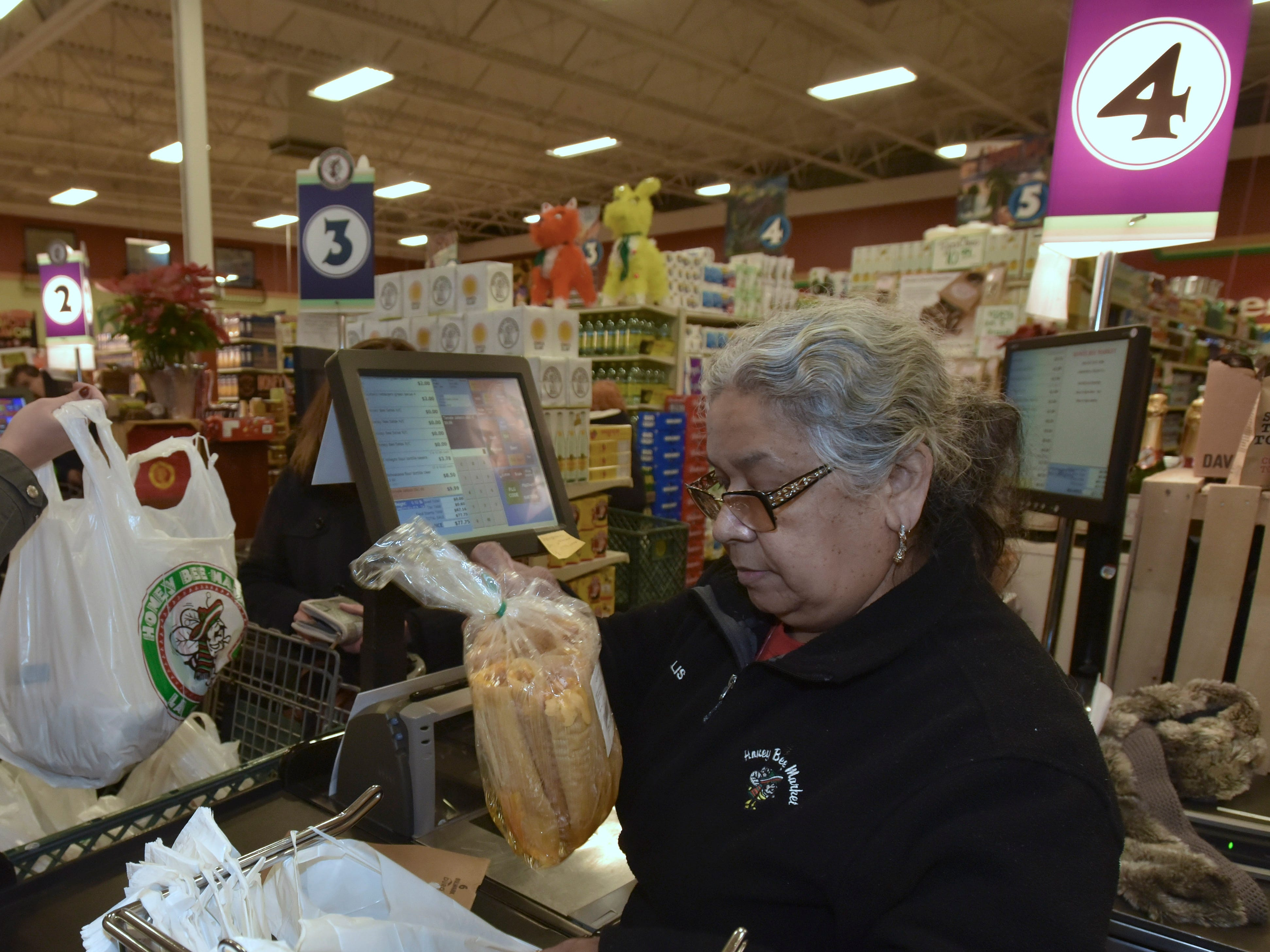 Beth Napier, left, of Trenton, puts grociers in her shopping cart as cashier Phyllis Zuniga, right, of Detroit, double bags a dozen fresh tamales.