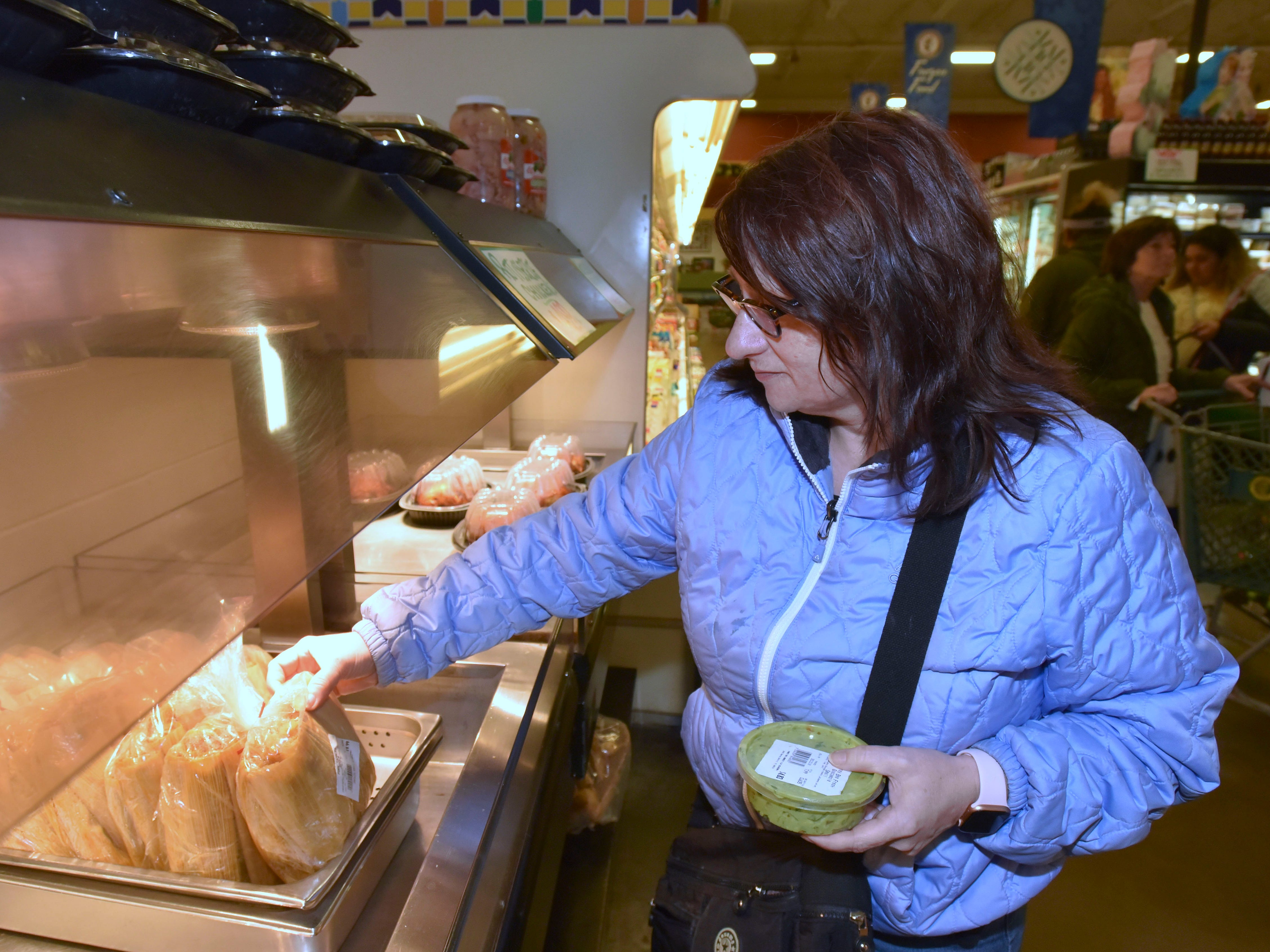Phyllis Walter, of St. Clair Shores, buys a dozen fresh tamales from the self-serve warming case.