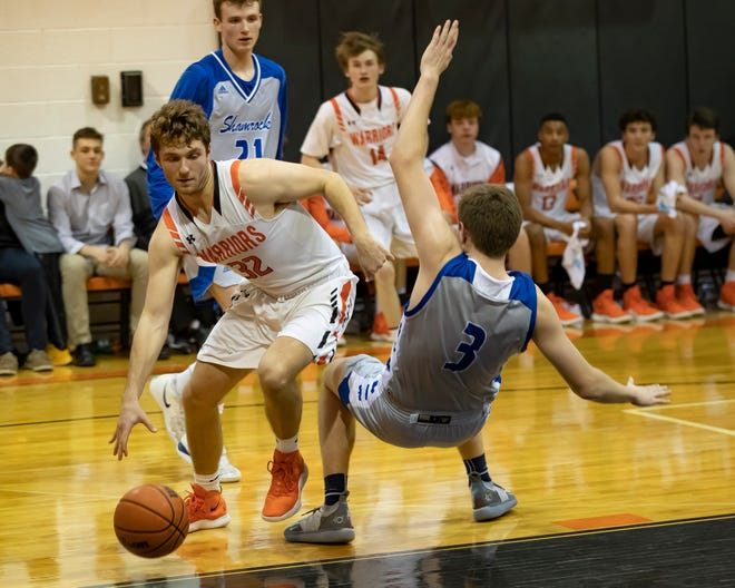 Davis Lukomski (3) of the Catholic Central Shamrocks draws a charging foul on James Mackenzie (32) of the Brother Rice Warriors in the second half during a high school basketball game at Brother Rice High School.