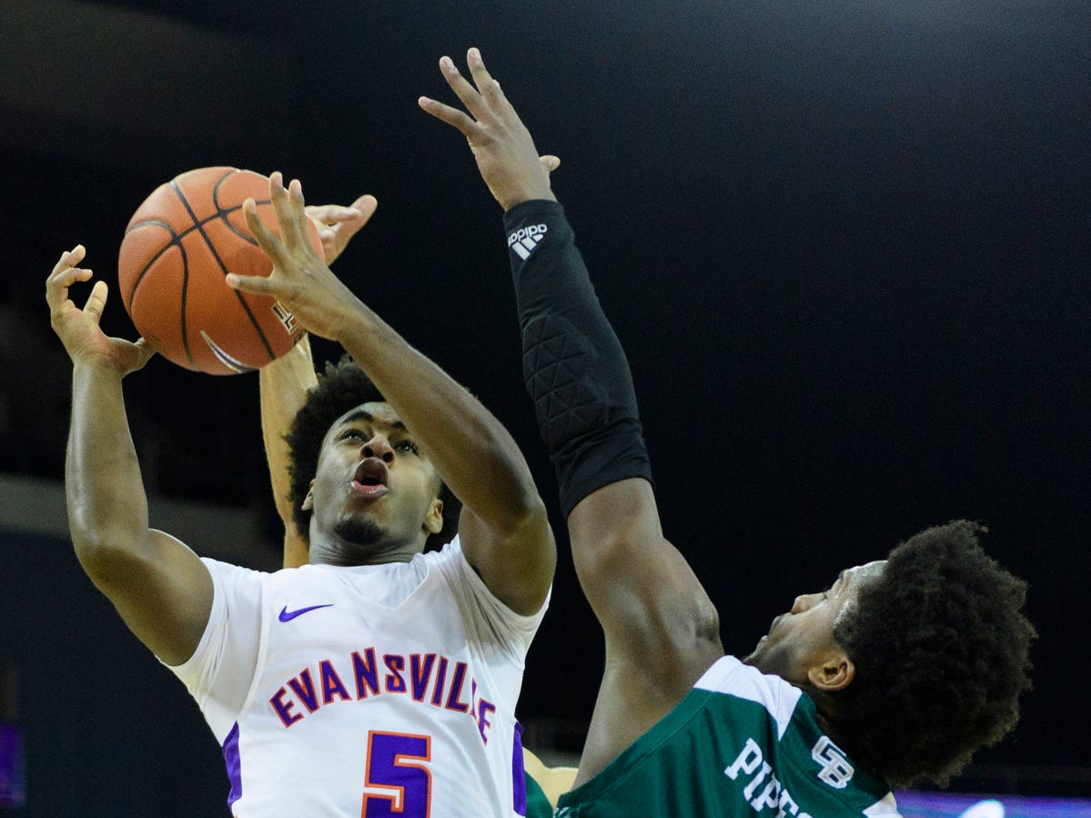 Green Bay's PJ Pipes (2) and Green Bay's Kameron Hankerson (21) block University of Evansville's Shamar Givance (5) from taking a shot during the first half at Ford Center in Evansville, Ind., Saturday, Dec. 22, 2018.
