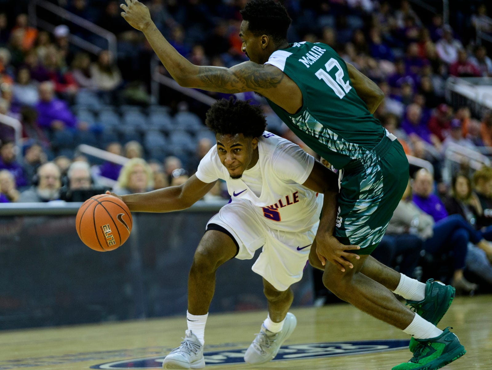University of Evansville's Shamar Givance (5) rushes past Green Bay's Josh McNair (12) during the first half at Ford Center in Evansville, Ind., Saturday, Dec. 22, 2018.