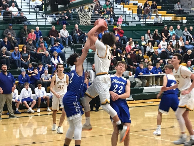 CMR's Bryce Depping, in white, shoots over Havre's Kellen Detrick (32, left) and Mason Rismon (22) during Friday's game at CMR Fieldhouse. The Rustlers won 64-42.