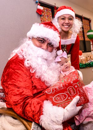 Santa Claus and Mrs. Claus, portrayed by Guam Police Department officers Vincent Perez and Joneen Terlaje, pass out a gift to a child attending the Children's Smiles For Hope event at the GPD's Dededo Precinct Command on Saturday, Dec. 22, 2018. The children were treated to a morning with story telling, snacks, a visit by Santa and Mrs. Claus and gifts to enjoy the holiday with. The event, held in partnership with the Chasing Rainbows End Organization and GPD, was attended by over twenty of the area's less fortunate younger population and their families.