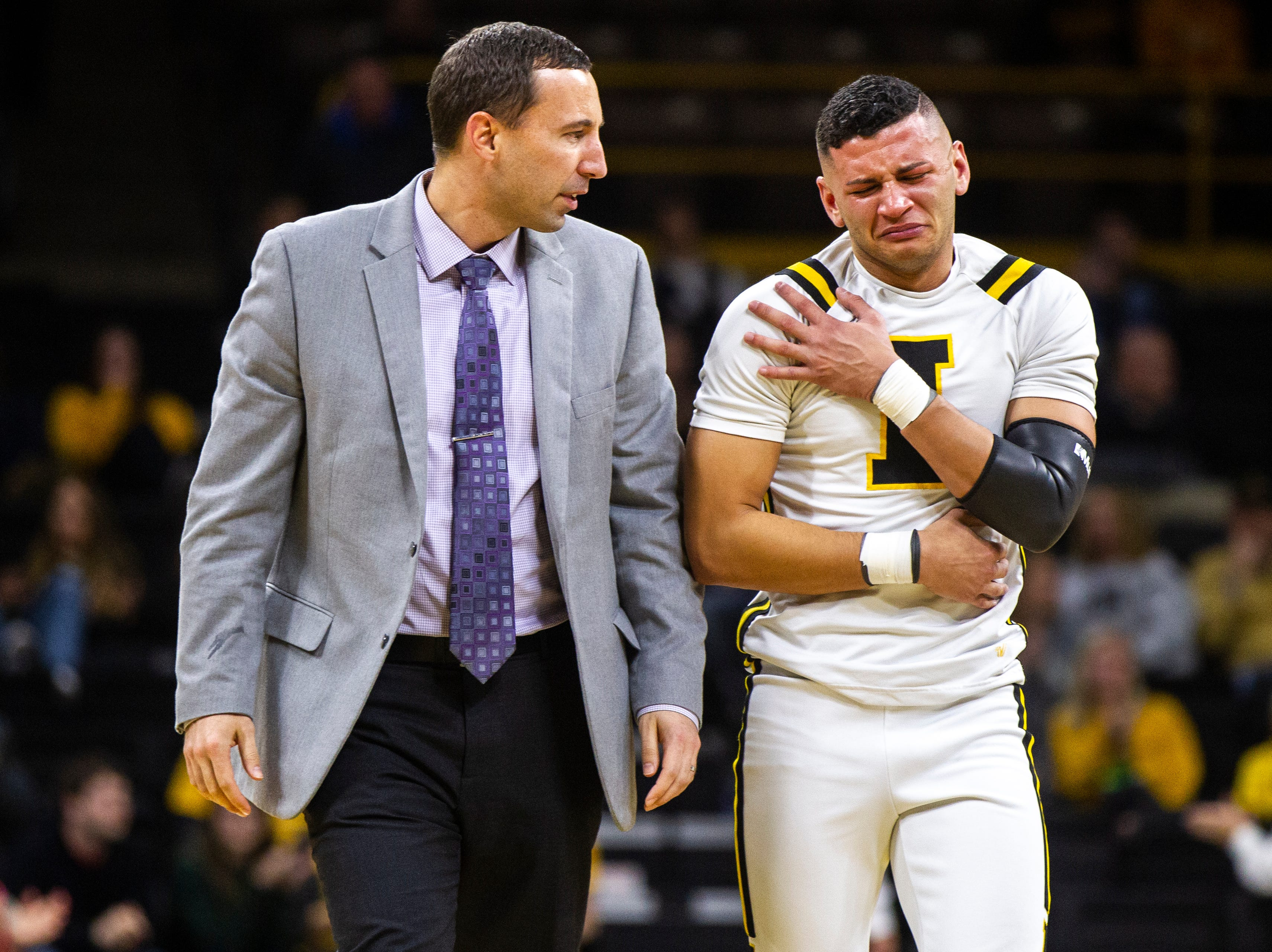 An Iowa cheerleader reaches for his shoulder after taking a fall during a timeout at a NCAA men's basketball game on Saturday, Dec. 22, 2018, at Carver-Hawkeye Arena in Iowa City.