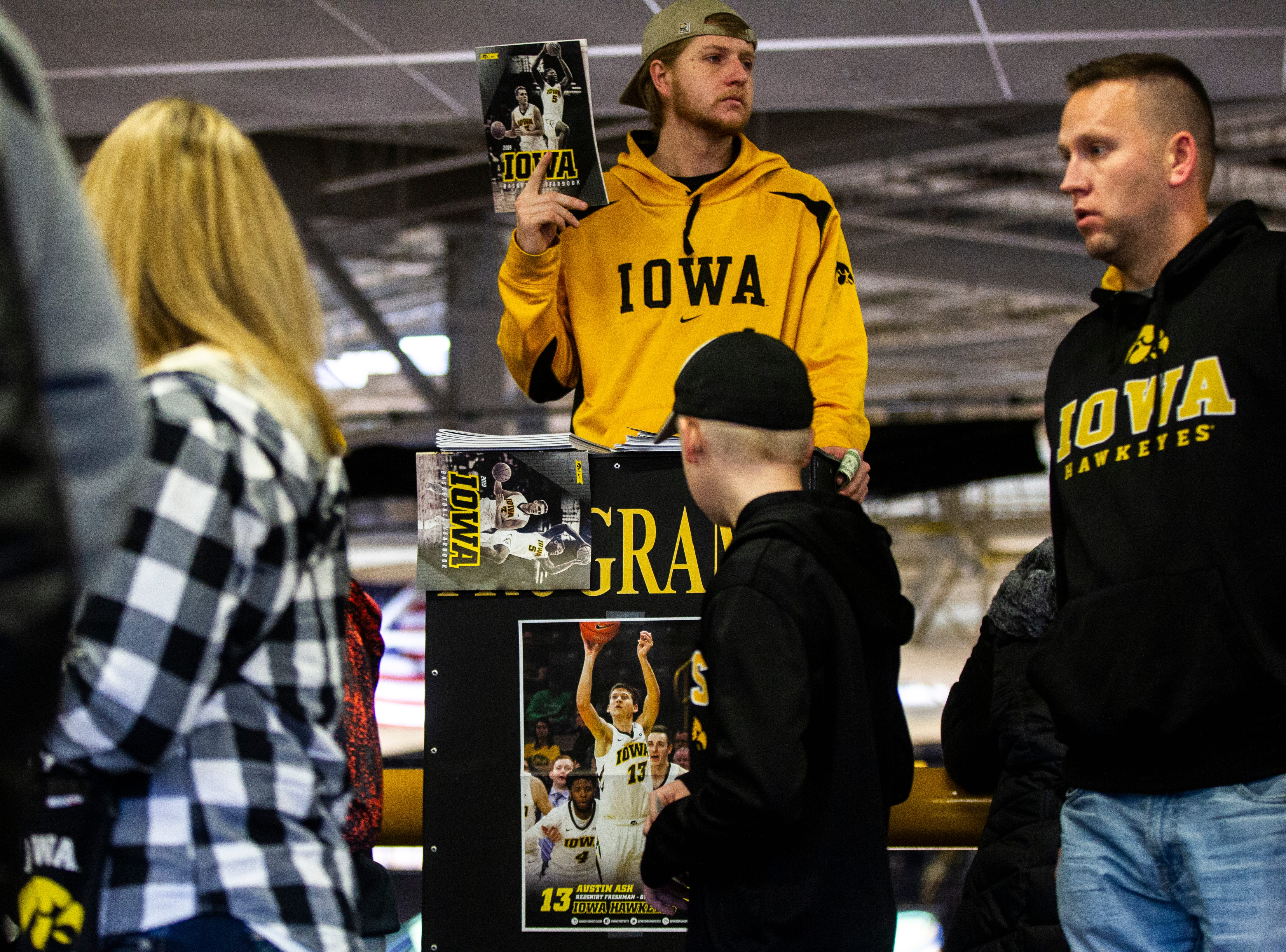 Fans walk past a podium featuring a poster of Iowa guard Austin Ash during a NCAA men's basketball game on Saturday, Dec. 22, 2018, at Carver-Hawkeye Arena in Iowa City.